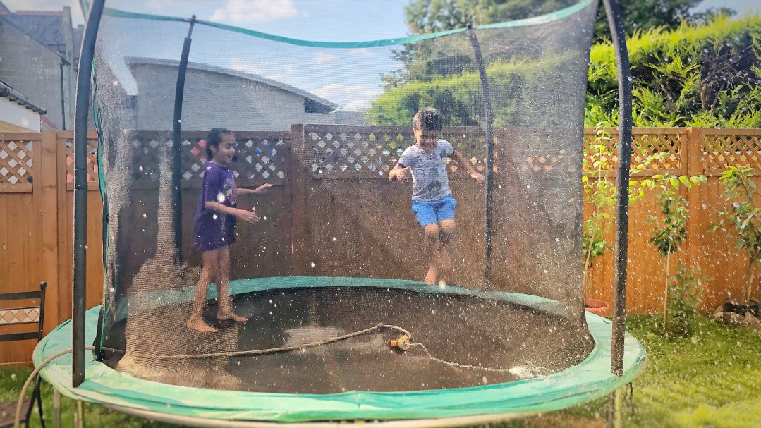 Kids jumping on a trampoline with a hose spraying water.