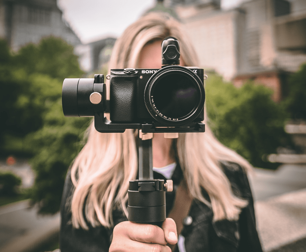 Woman holding camera and using multimedia skills.