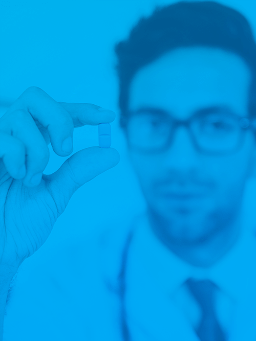 Male doctor with glasses holds up a small prescription pill