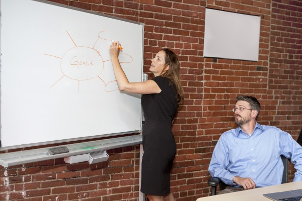 woman writing goals on white board