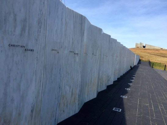 The Wall of Names features slabs of marble bearing the names of each victim. The Visitor Center stands in the background. Photo courtesy of author.