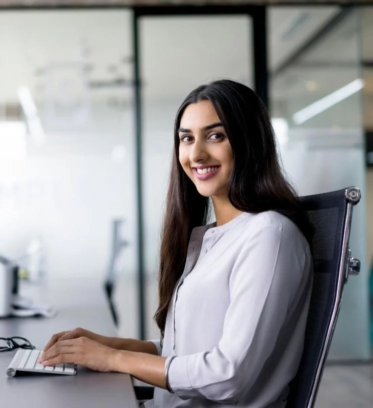 Woman Virtual Assistant sitting at office desk