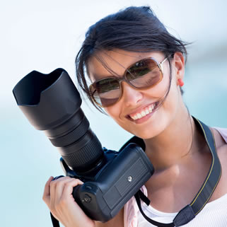 Beautiful female photographer smiling while holding her camera ready to take pictures