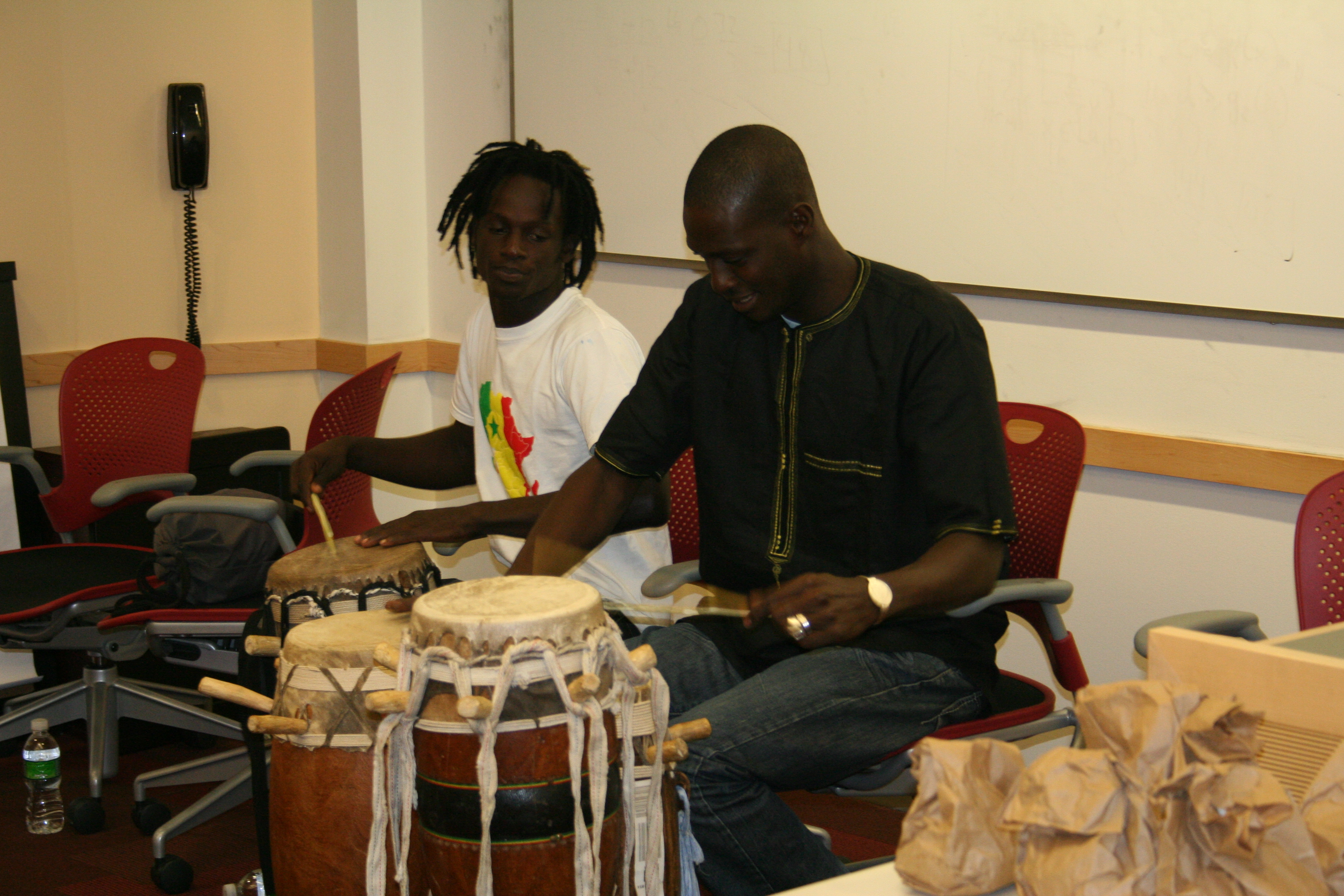 Moustapha Faye and Malick Ngom demonstrate the sabar drum and its rhythms to Suffolk University.