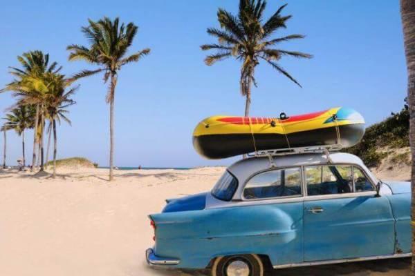 Sahilde üstünde şişme bot olan eski mavi araba