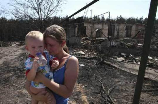 A woman in Voronezh, Russia, held a crying baby near the remains of her burnt-out home.