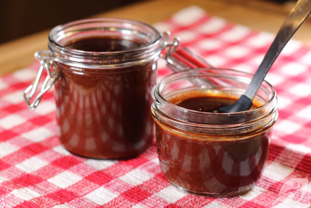 Two canning jars of Homemade BBQ Sauce on a red checker placemat.