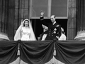 Queen Elizabeth in a wedding dress and Prince Philip in uniform wave to their subjects from the balcony of Buckingham Palace after their wedding