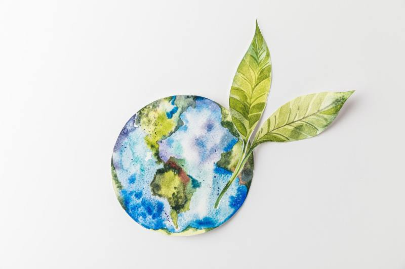 top view of handmade colorful paper globe with green leaves isolated on grey, environment protection