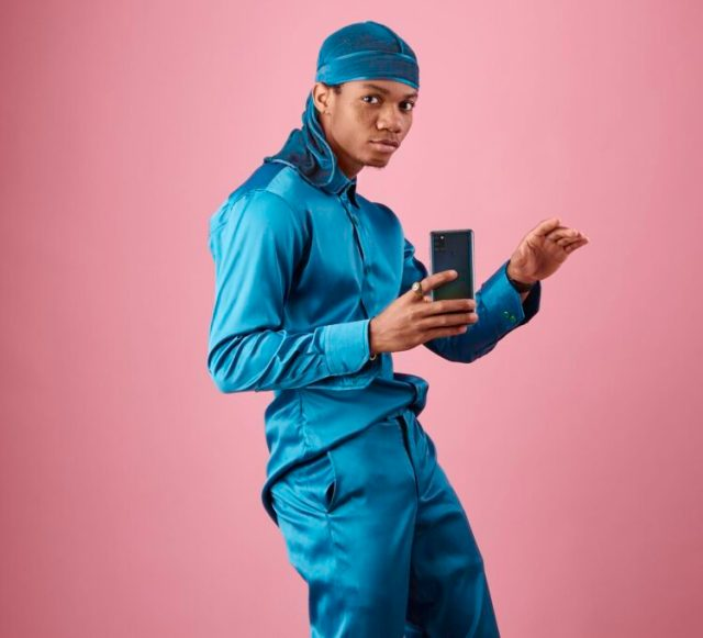 KiDi wearing a blue atire with a dreke on his head holding a samsung phone in a pink background - KiDi - Next Time I See You