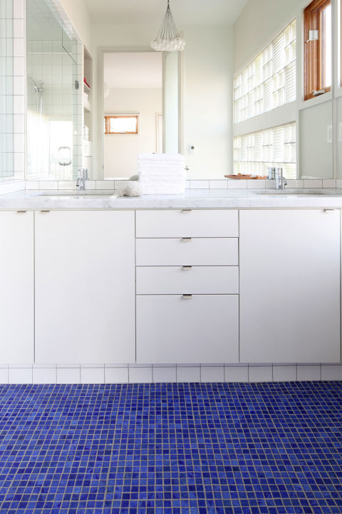 If you can't commit to an all-white space, add a pop of color at your feet. Bright blue floors warm up an otherwise stark room.