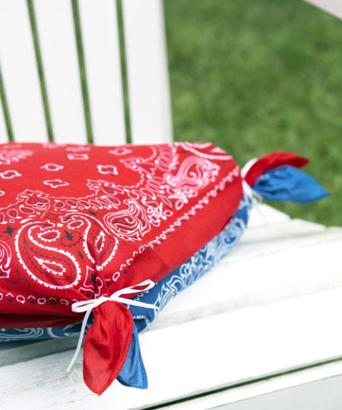 Soften outdoor chairs with no-sew pillow covers crafted from contrasting bandannas. Sandwich one cushion between two scarves, then join each corner together with a rubber band and hide bands with thin ribbon, as shown.