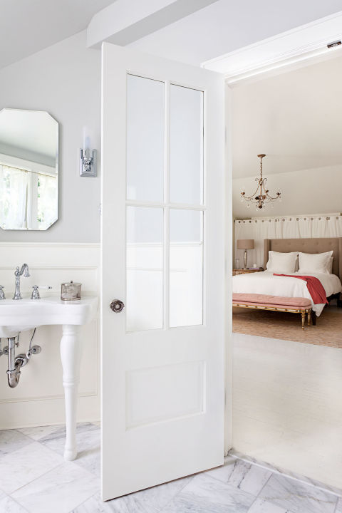 Maximize sunlight with a pure white color scheme and shiny hardware that reflects rays. In a Connecticut cottage, the windowed doors also let light in from the adjoining bedroom.