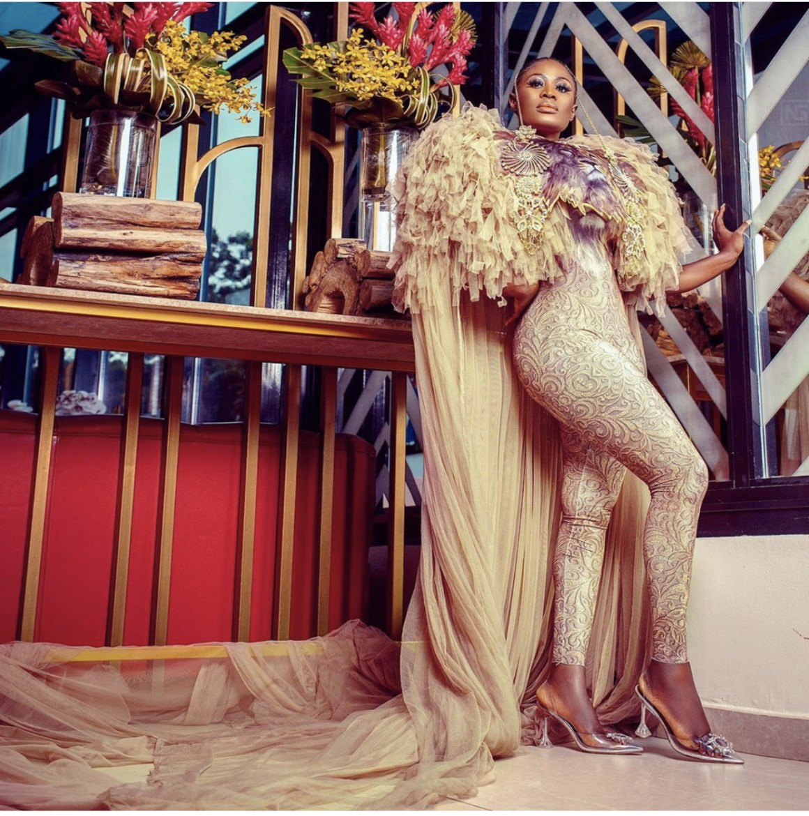 Beyonce wore a custom-made glittering feathery golden catsuit featuring the image of a lion across the bodice and a matching cape and we can see the same thing in Nana Akua Addo's picture.