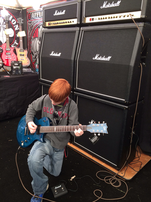 Student playing guitar at The Crazy Dave's Music Experience