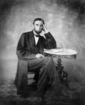 President Lincoln sitting at a table with arm on a book