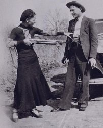 Bonnie with a shotgun reaches for officer Persell's pistol in Clyde's waistband.