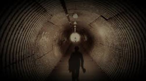 Figure in a tunnel looking to a light