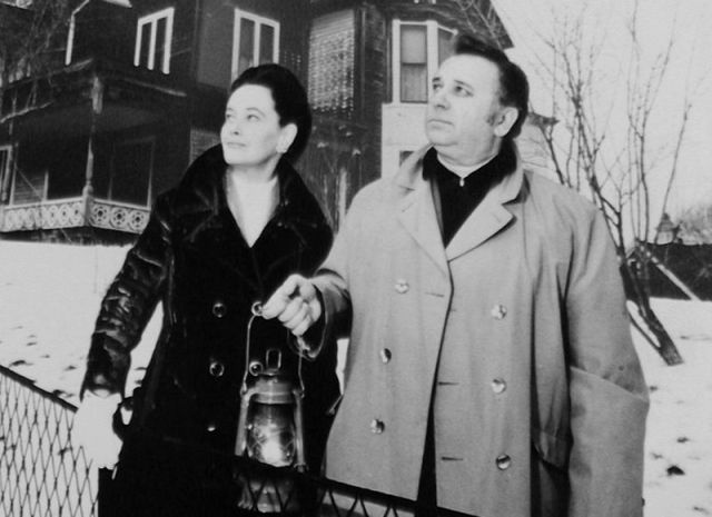 Ed and Lorraine Warren outside a house. Ed is holding a lantern