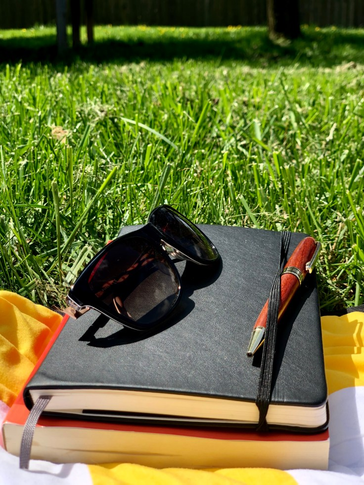 Journal and sunglasses in yard.