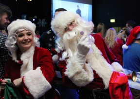 """DCU SU Welfare Officer Eve Kerton helps a mysterious Santa Claus distribute lollipops during the traditional SU Christmas Ball last Wednesday in the Hub. The theme of this year's ball was RTE's """"Toy Show""""."""