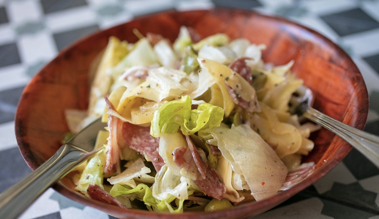 Italian chopped salad with salami, artichokes, pickled peppers, olives