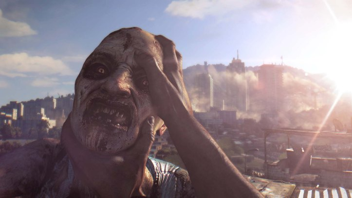 Dying Light. The player grapples with a zombie in a distributing close-up view with one hand pressed against its head and the other around its chin.