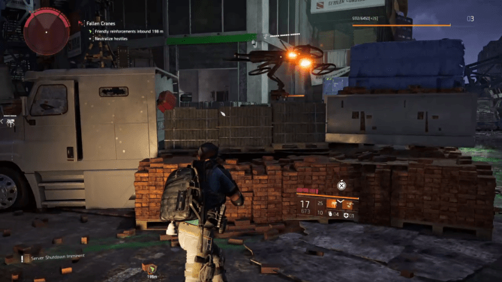 An agent takes cover behind some piled up bricks in The Division 2.