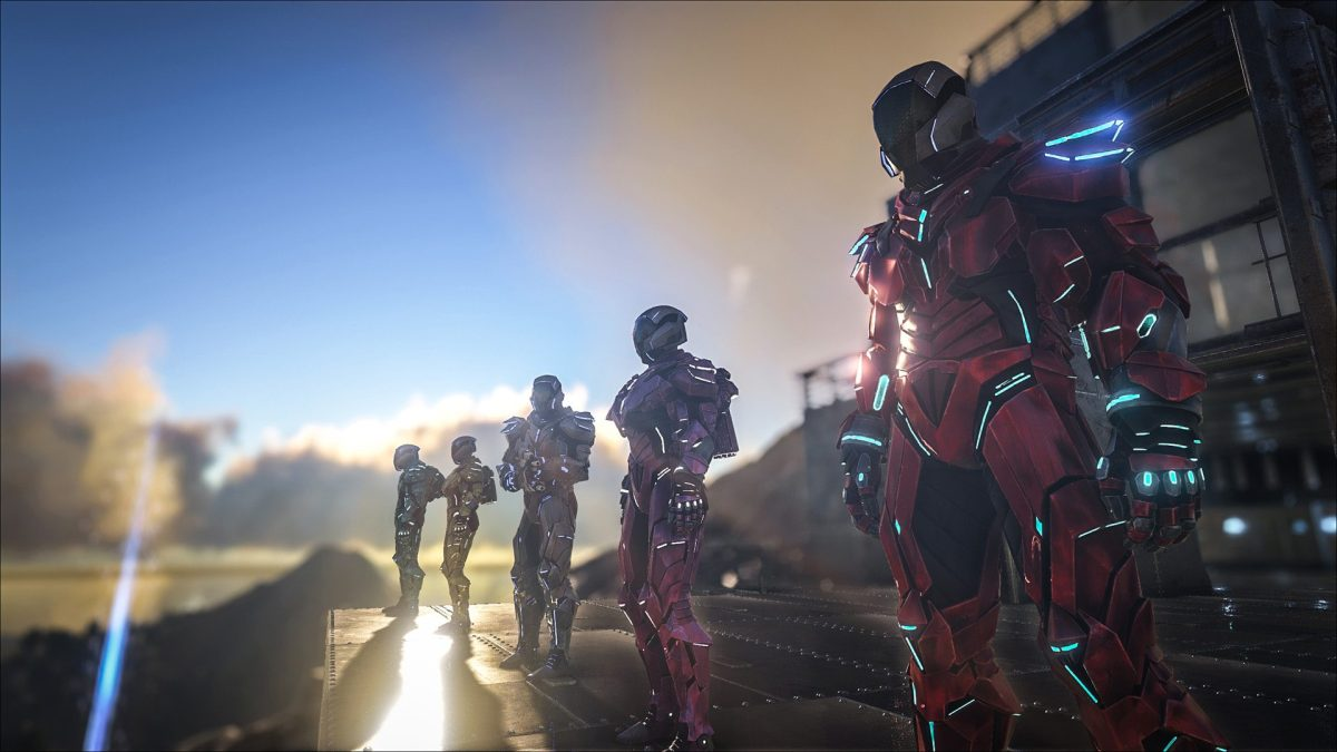 A group of players stand outside of a base wearing tech suits in Ark.