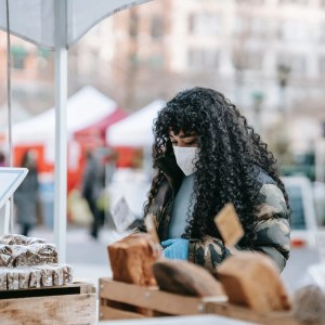 black woman in mask choosing food in street bakery