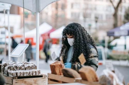 black woman in mask choosing food in street bakery