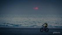 Vélo sur la plage au crépuscule - Photo : Gilderic
