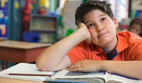 A child is daydreaming in a classroom.