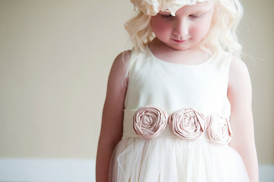 An Ivory Flower Girl Dress With Blush Pink On The