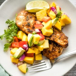 White plate with a serving of jerk chicken and mango avocado salsa.