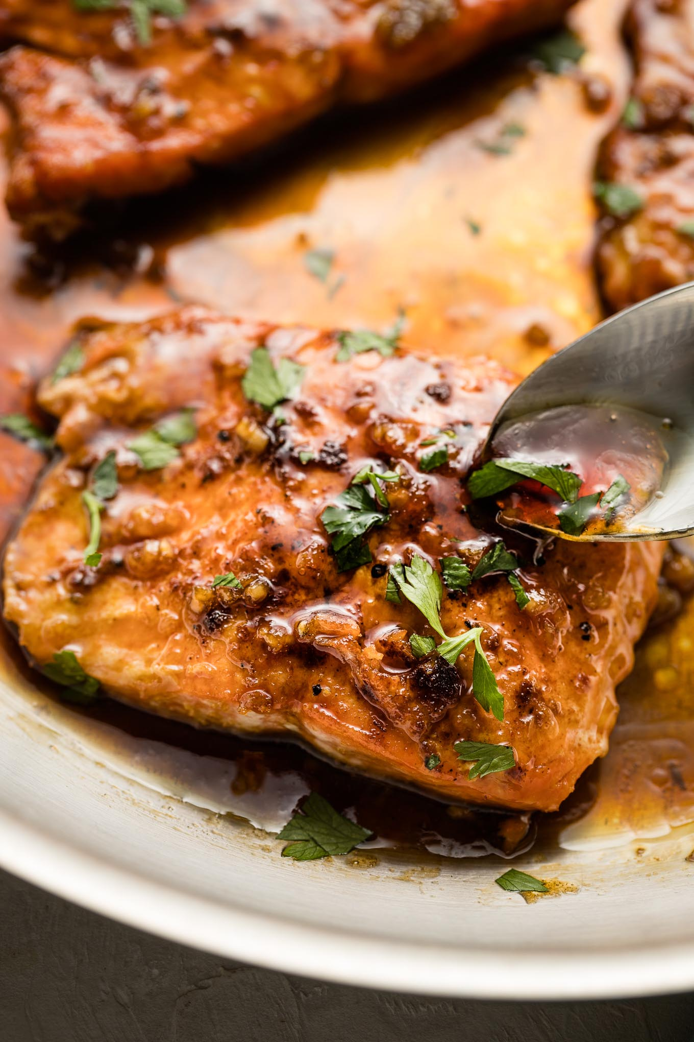 Spoon pouring sauce over cooked salmon filets.