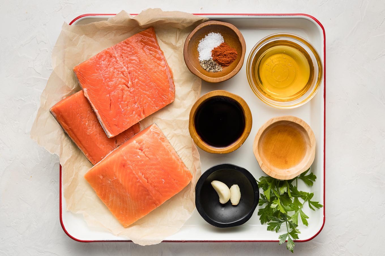 Salmon filets, seasonings, soy sauce, honey, apple cider vinegar, and parsley.