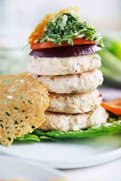Chicken Caesar Burgers stacked on lettuce and topped with onions and tomato