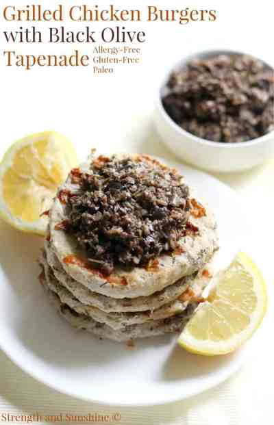 Grilled chicken burgers topped with black olive tapenade on a plate with lemons