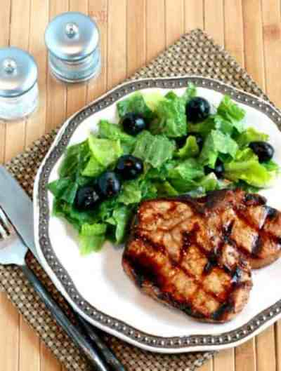 Grilled ginger soy pork chop and salad on plate