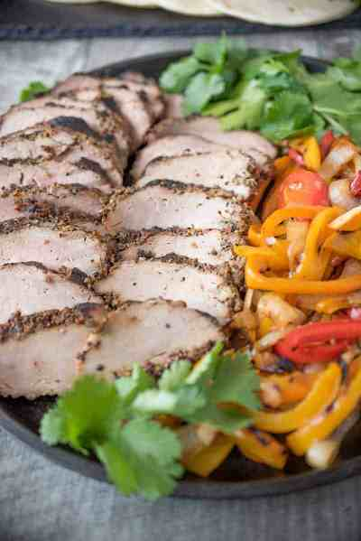 Grilled pork tenderloin fajitas and peppers on plate