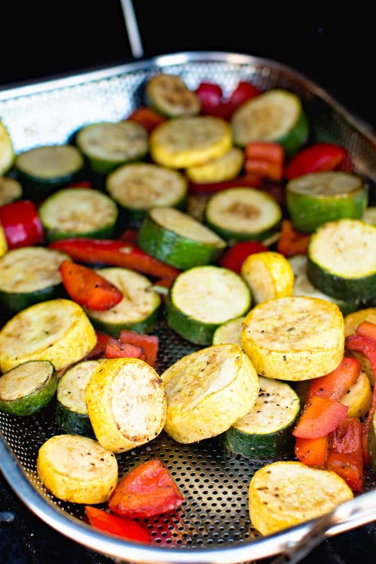 Grill pan with a mixture of green and yellow zucchini and peppers plus seasonings on a smoker