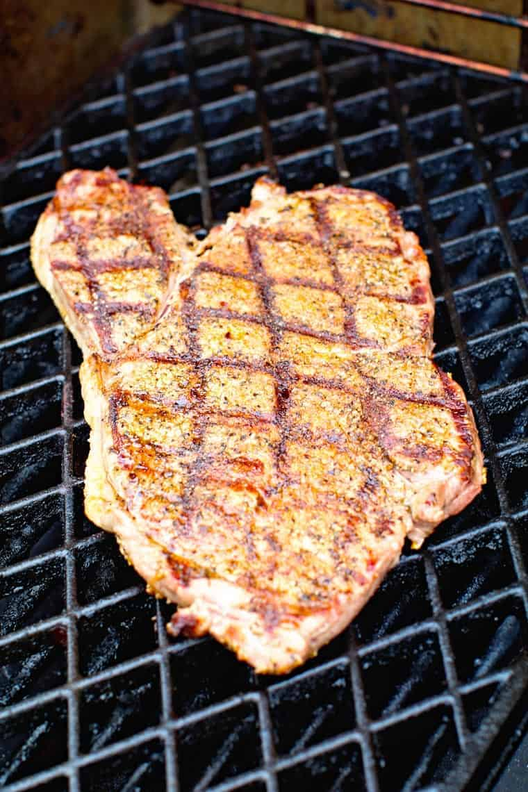 Steak on grill grates that has been seasoned and cooked on gass grill with sear marks on it