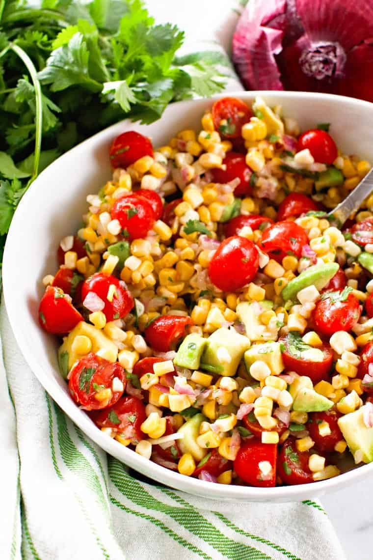 Corn Salad in white bowl with cilantro and red onion behind it
