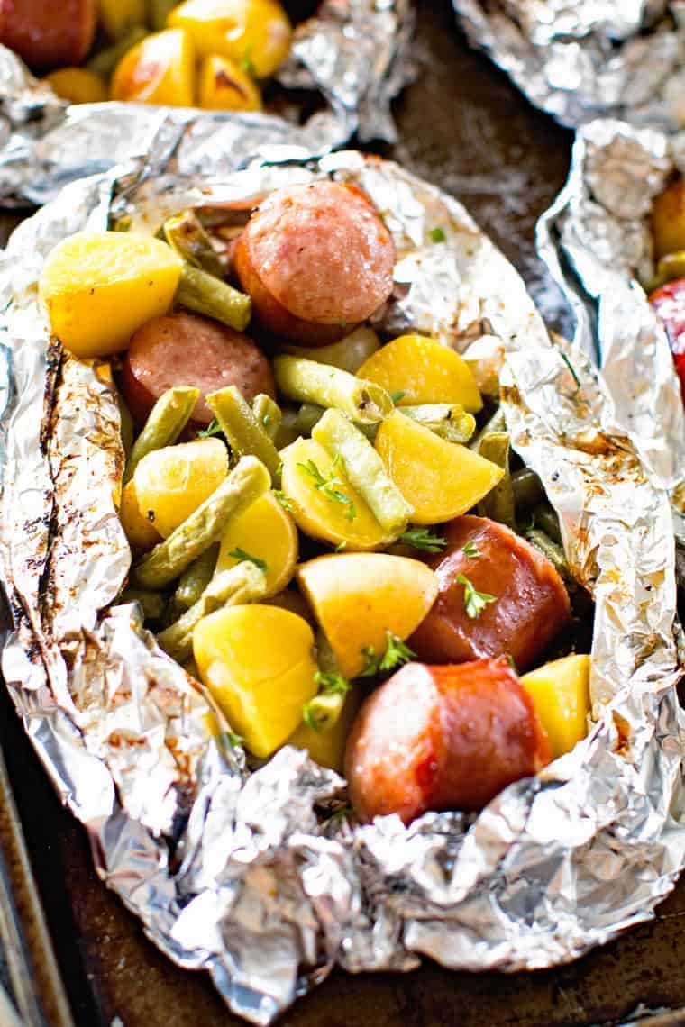 Grilled sausage foil packets filled with vegetables and sausage