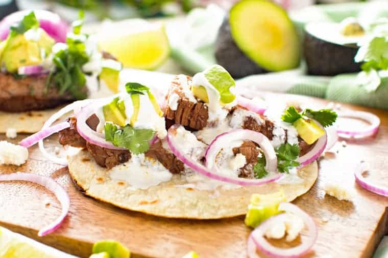 Flank steak tacos on a wooden curling board topping with cilantro, red onion and avocado.