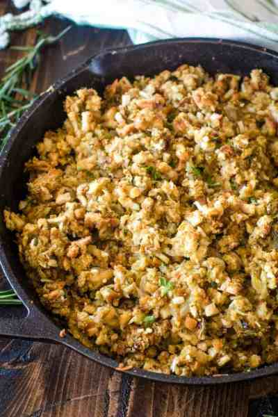 Cast iron skillet filled with smoked stuffing on a cutting board
