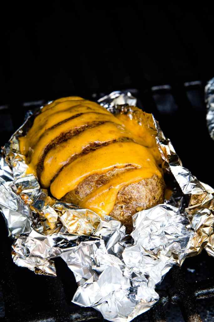 Hasselback Potatoes stuffed with cheese sitting on a piece of aluminum foil on a smoker rack.