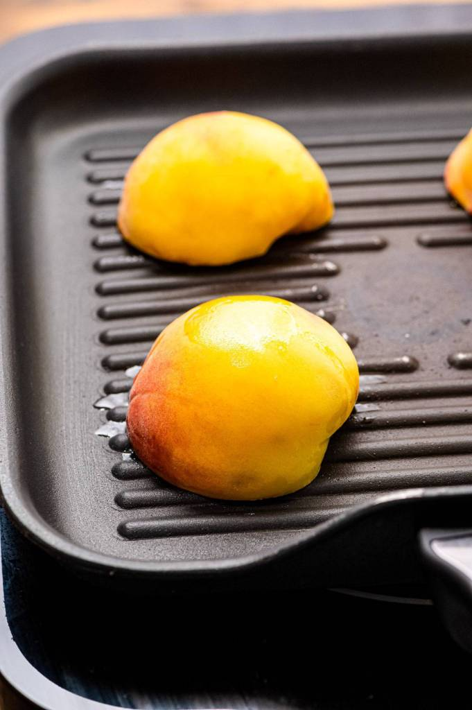 Peach halves face down on grill pan