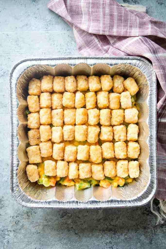 Square foil pan with cheese mixed vegetables in the bottom and topped with frozen tater tots